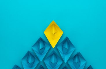 A yellow paper boat leading blue paper boats