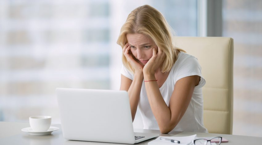disheartened woman stares at laptop