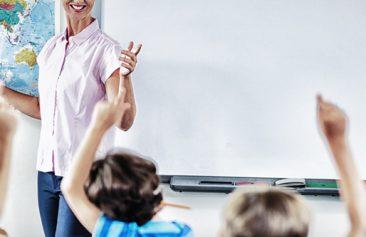 Teacher teaching kids in classroom at school
